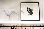 Framed art and white bird figurines above a rod hung with clothing