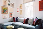 A blue sectional couch and a pair of green stools in a family space