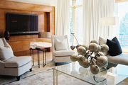 A pair of upholstered chairs and a glass-topped coffee table with gold oversize grapes