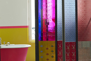 A bright-pink painted claw-foot tub and patterned floor tile in a Paris bathroom