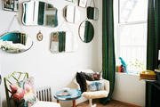 A grouping of mirrors hung above a room with a zebra-print rug and green patterned curtains