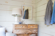 A rustic wood dresser occupies the corner of a whitewashed bedroom
