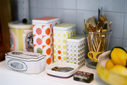 Patterned storage tins and a glass of gold flatware in a kitchen
