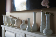 An array of milk glass vases atop a mantle