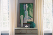 White curtains and a gray dresser decorated with art and pottery