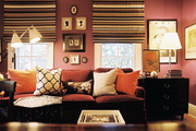 Striped roman shades and a grouping of framed silhouettes in a purple family space