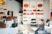 Colorful leather handbags and accessories arranged on white shelves