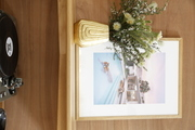 A framed photograph and a vase with a dried floral arrangement on a wooden shelf.