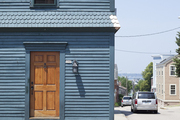 A lightly weathered wooden door on a blue house
