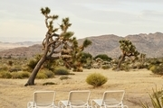 A desert setting with three lawn chairs set up outside.
