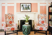 Pink paneled walls and a pair of floral wingback chairs with a garden stool