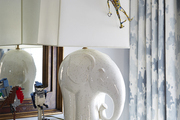 White elephant shaped lamp atop modern white dresser