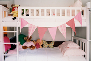 A white bunk bed in a children's room