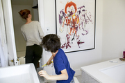 Oversize kids' art framed and hung in a bathroom by a tub
