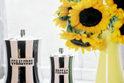 Cheeky striped storage containers and a vase of flowers on a shelf covered with white tile