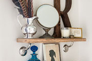 Antique details on shallow shelving in a small powder room