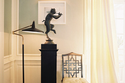 A grouping of a black fretwork chair, a floor lamp, and a statue on a pedestal
