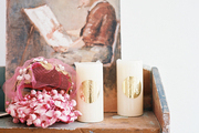 A collection of white candles and a vintage painting on a wooden bookshelf