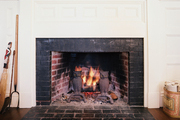 Owl andirons in a brick fireplace with a white surround