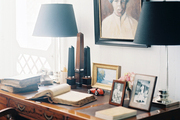 A wooden desk with a pair of clear lamps with black shades