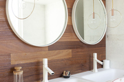 Twinned hanging lamps, round mirrors, and white sinks against a wood-paneled bathroom wall