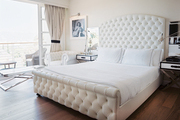 A white bedroom anchored by a tufted bed