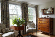A pair of grain sack upholstered armchairs beside a dresser in a guest bedroom