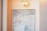 A crystal light fixture suspended above a painting in a hallway
