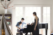 Andrew Bird, Katherine Tsina, and their son gathered around a piano in the living room of their Los Angeles home