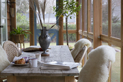 Sheepskin throws over chairs surrounding a reclaimed-wood table on a Hamptons screened porch