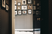 A white sheepskin throw in a wallpapered hallway hung with art
