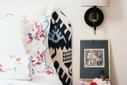 An ikat-upholstered headboard and scalloped bed linens