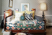 Layered textiles on a wooden daybed against patterned wallpaper