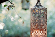 A punched-metal lantern suspended from a tree branch