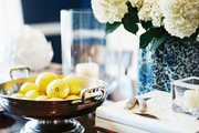 A footed bowl of lemons and a blue-and-white vase of flowers on a wooden tabletop
