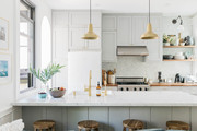 A contemporary kitchen with gold pendant lamps and white countertops.