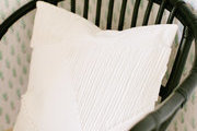 A detail of a black rattan chair and a white pillow.