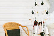 A rattan chair next to a wooden Christmas tree.