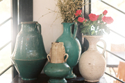 A grouping of pottery on a red cabinet