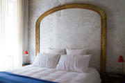 Gold headboard hanging over white bedding.