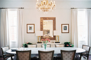 Upholstered dining chairs surrounding an oval table and a crystal chandelier overhead