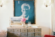 Art arranged above a rustic wood console