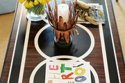 Flowers and books atop a wooden coffee table with a black-and-white pattern