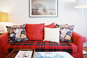A red couch topped with floral pillows and a plaid throw