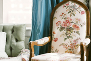 A floral armchair beside a tufted chair and flowing blue curtains