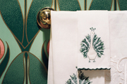 Monogrammed and embroidered hand towels in a powder room with floral wallpaper