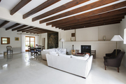 A living room and dining area with exposed beams