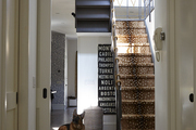 Patterned area rugs in white hallway leading to animal print stairs.
