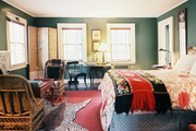 A mix of patterns in a green-walled bedroom