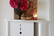 A wall nook holding a vase and candle arrangement.